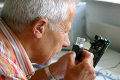 Older man trying to read the tiny letters on printboard. Older man trying to read the tiny letters on the printboard he is repairing Royalty Free Stock Images