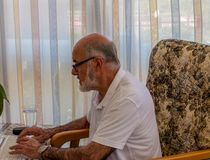 Older man typing on laptop. Older man  sitting in the chair with laptop ant typing royalty free stock photos