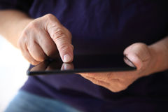 Older man uses his tablet Royalty Free Stock Images