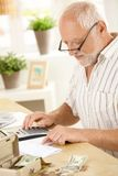 Older man using calculator at home Royalty Free Stock Photography