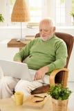 Older man using laptop computer at home. Smiling older man sitting in armchair using laptop computer at home Stock Photo