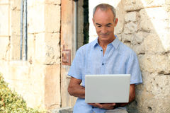Older man using a laptop computer Stock Photo
