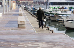 An older man walks along attached boats in port Tarragona. Spain 04.01. 2016. An older man walks along attached boats in port Stock Image