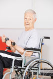 Older man in wheelchair training with dumbbells Stock Photography