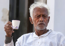 Older man with white hair drinks coffee. Stock Images