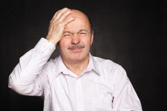 Older man in white shirt hugged his head, wincing. Despair and  pain of failure or disease Stock Photography