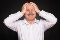 Older man in white shirt hugged his head, wincing. Despair and  pain of failure or disease Royalty Free Stock Images
