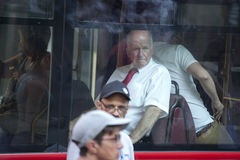 An older man in a white shirt with short sleeves and a red tie looking through the window of the bus Stock Photo