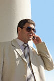 Older man in a white suit calling. An elderly businessman will ring. Sunny, summer royalty free stock photos