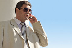Older man in a white suit calling. An elderly businessman will ring. Sunny, summer stock image