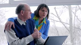 Older man and woman with laptop spend time on internet on vacation in room. Near window stock video