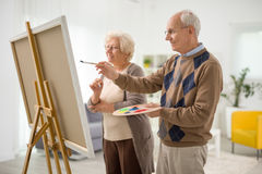 Older man and woman painting on canvas. Older men and women painting something on a canvas with paintbrushes at home royalty free stock image