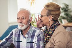 Older man and woman or pensioners with a hearing problem stock photo