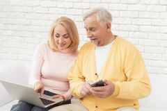 An older man and woman are sitting on a big white sofa and watching something on the laptop screen. An older men and women are sitting on a big white sofa and Stock Photography