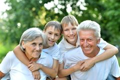 Older man and woman with their grandchildren. Older men and women with their grandchildren having fun outdoors stock photography