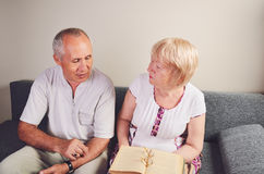 Older man and woman 60-65 years old talking, discussing book Stock Photo