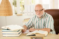 Older man working at his study. Portrait of older man working at his study, taking notes, using books, looking at camera Stock Images