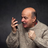 Older man yells into the phone in anger. Royalty Free Stock Photos