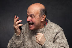Older man yells into the phone in anger. Stock Photography