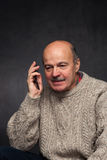 Older man yells into the phone in anger. Royalty Free Stock Image