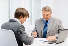 Older man and young man having meeting in office. Business, technology and office concept - older men and young men having meeting in office Stock Images