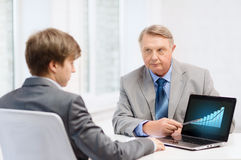 Older man and young man with laptop computer Stock Photo