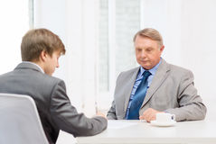 Older man and young man signing papers in office Stock Photo