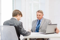 Older man and young man signing papers in office Royalty Free Stock Images
