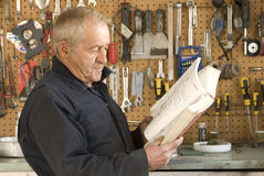 Older Mechanic Reading. An older man reading a mechanic's book in the garage, standing in front of hanging tools Stock Photo
