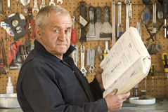 Older Mechanic Reading. An older man reading a mechanic's book in the garage, standing in front of hanging tools Royalty Free Stock Photo