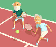 Older men playing tennis doubles at court. View of doubles player hitting tennis ball with forehand on court. Royalty Free Stock Photos