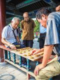 Older men playing traditional Chinese chess. Beijing, China - September 2017: Older men playing traditional Chinese chess in the long corridor of the Temple of Royalty Free Stock Photo