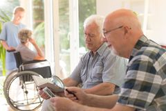 Man reading a book. Older men reading a book and another men watching photos with the use of magnifier Royalty Free Stock Images