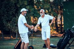 Free Older Men Stand On A Golf Course And Talking Royalty Free Stock Photos - 214378498