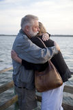 Older Middle-Aged Couple Hugging on Dock. Older middle-aged man and woman affectionately hugging on a dock at the end of the day, illuminated by the setting sun Royalty Free Stock Photography