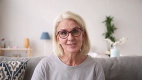 Older woman looking at camera talking laughing making video call stock footage