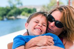 Older mom teasing son with kisses Royalty Free Stock Images