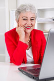 Older office worker with laptop Royalty Free Stock Photography