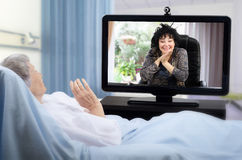 Older patient has video chat on hospital bed Stock Photos