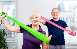 Elderly couple in senior gymnastic class doing workout with rubb. Older patients in physiotherapy using power band for strength training Royalty Free Stock Image