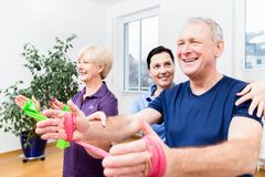 Physio showing senior couple how to use rubber band as expander Royalty Free Stock Images