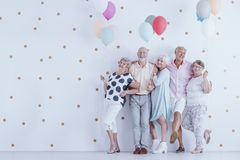 Older people with balloons. Happy older people smiling and standing with colorful balloons at the New Year`s Eve party photo Royalty Free Stock Images