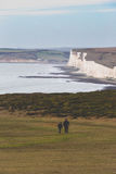 Older people couple walk through Seven Sisters Cliffs in England Royalty Free Stock Photos