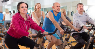 Older people do sports on exercise bikes. Satisfied older people do sports on exercise bikes. focus on the left woman Stock Photo