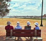 Older people facing the sea sit on bench. Older people facing the sea sit on a bench couple beach summer view adult elderly ocean relax senior sitting together royalty free stock photos
