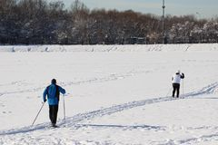 Older people go in for sports - skiing in winter. Winter, a lot of snow, cold, sports pensioners. Old women and men skiing in the park stock image
