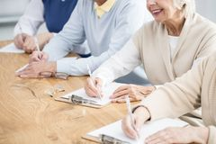 Older people during lecture. Older happy people writing a test during IT lecture stock photography