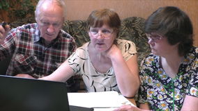 Older people at the table with a notebook. At home stock footage