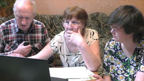 Older people at the table with a notebook. At home stock video