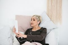 An older positive woman uses a tablet to watch videos, listen to music and chat with friends on social networks. stock images
